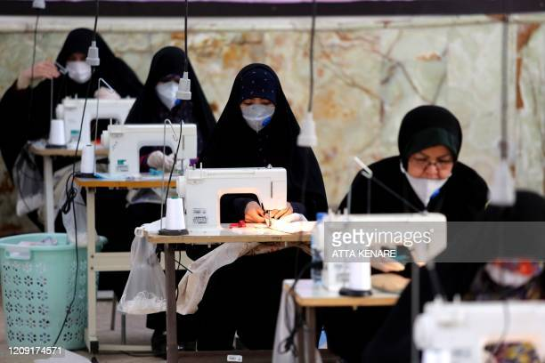 Iranian women, members of paramilitary organisation Basij, make face masks and other protective items at a mosque in the capital Tehran, amid the...
