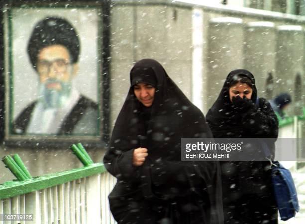 Iranian women pass a portrait of the Islamic Republic's supreme leader Ayatollah Ali Khamenei under heavy snowfall in Tehran 24 January 2001. Primary...