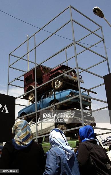 Iranian women pass by old Iranian manufactured cars displayed during the annual car fair in Tehran 22 June 2004 Iran's car producers already the...