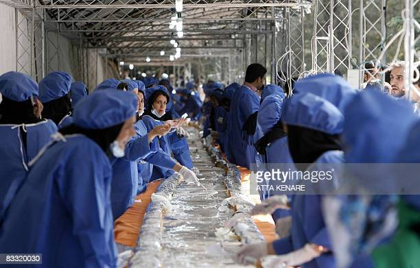 Iranian women prepare a giant ostrich meat sandwich planned to reach 1,500 meters in an attempt to achieve a 'Guinness World Record', during the...