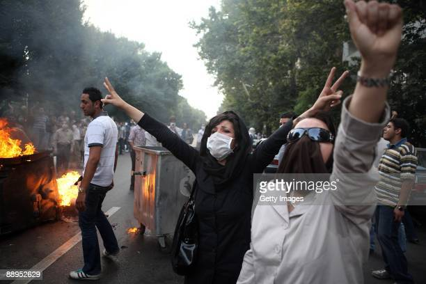 Iranian women raise their arms in protest as demonstrators burn rubbish in the streets on July 9, 2009 in Tehran, Iran. Following recent unrest in...