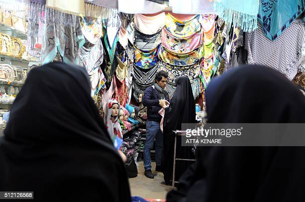 Iranian women shop for scarves at the ancient Grand Bazaar of the holy city of Qom 130 kilometres south of Tehran on February 24 2016 Women make up...