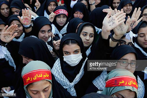 Iranian women show their palms bearing slogans praising the current Iranian Supreme Leader outside the former US embassy in the Iranian capital...