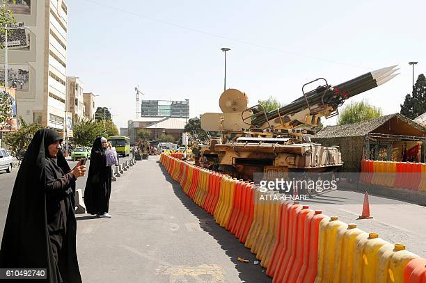Iranian women take pictures of Sam6 missiles displayed in the street during a war exhibition to commemorate the 198088 IranIraq war at Baharestan...