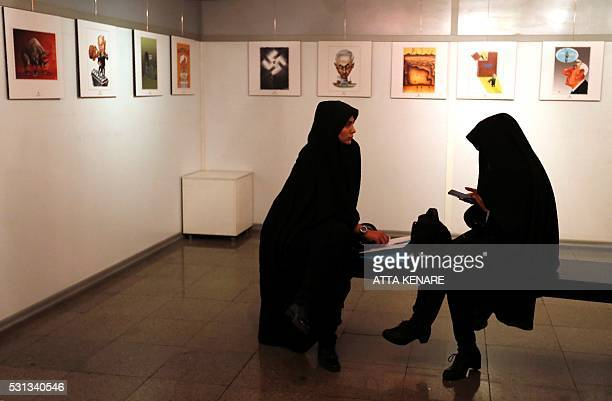 Iranian women visit the second international exhibition of drawing and cartoons on the Holocaust in Tehran on May 14 2016 Some 150 drawings from...