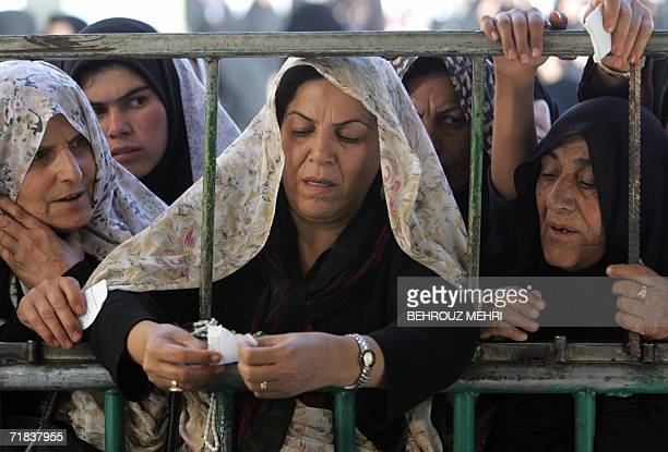 Iranian women wait to pass down their messages to Mahdi through a symbolic well in the courtyard of the Jamkaran mosque outside the religious city of...