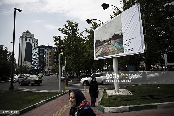 Iranian women walk past a billboard displaying the 'Flower beds in Holland' painting by Dutch impressionist painter Vincent van Gogh on a square in...