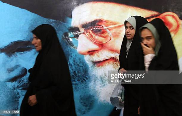 Iranian women walk past a giant poster featuring the founder of Iran's Islamic Republic Ayatollah Ruhollah Khomeini during the ceremony marking the...