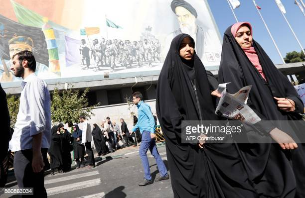 Iranian women walk past a portrait of late Iranian supreme leader Ayatollah Ruhollah Khomeini following the weekly Friday prayer in Tehran on October...