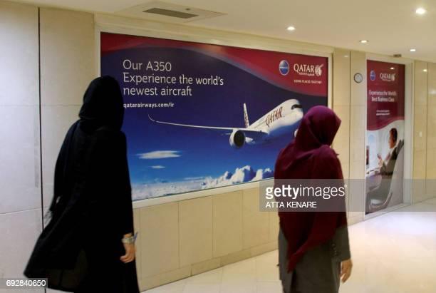 Iranian women walk past a Qatar Airways branch in the capital Tehran on June 6 2017 A ban on Qatari flights imposed by Saudi Arabia and its allies...