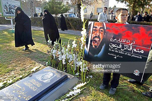Iranian women walk past as a boy holds a placard near a newly laid tombstone to honour Khaled Eslamboli the assassin of former Egyptian president...