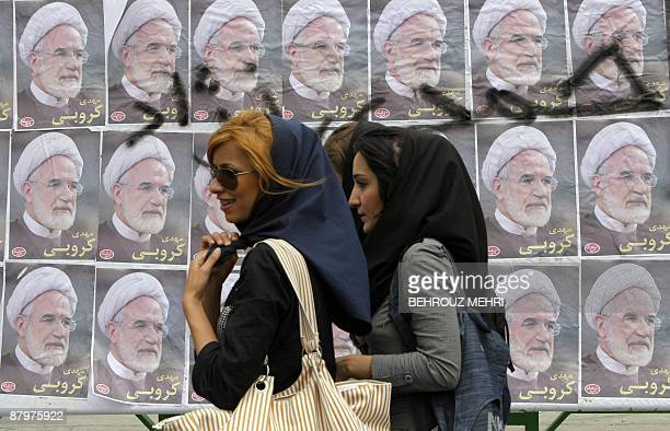 Iranian women walk past portraits Mehdi Karroubi the reformist former parliament speaker running in the June presidential elections in downtown...
