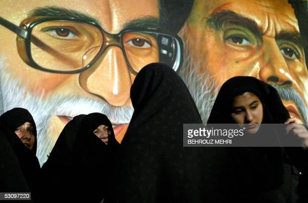 Iranian women wearing black Chador queue up to vote for the presidential elections in front of a portrait of Iran's supreme leader Ayatollah Ali...
