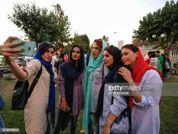 Iranian women wearing facepaint of the national flag pose for a selfie photograph with a cell phone outside Azadi stadium in the capital Tehran on...