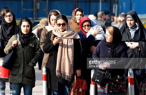Iranian women wearing hijab walk down a street in the capital Tehran on February 7 2018 A spate of unprecedented protests against Iran's mandatory...