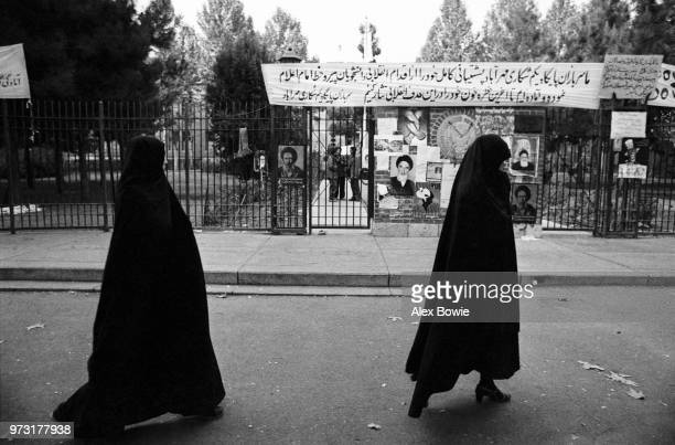 Iranian women wearing the traditional 'chador' walk past the main entrance of the former US Embassy that is now defaced with religious posters and...