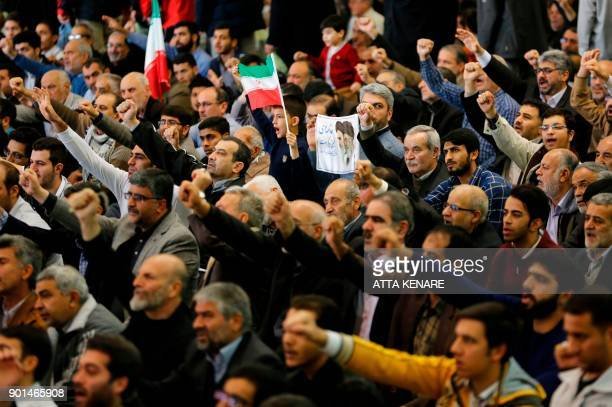 Iranian worshippers raise their fists during the Friday Prayer ceremony at the Imam Khomeini mosque in Tehran on January 5 2018 New proregime...