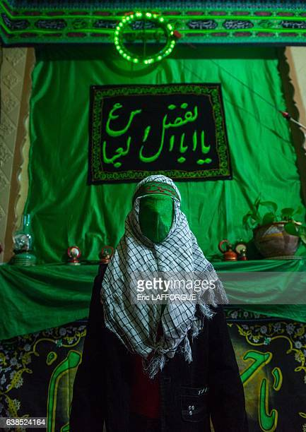 Iranian young man with green veil covering his face during Chehel Menbari festival on Tasua to commemorate the martyrdom of Hussein on October 23...