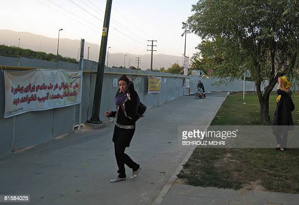 Iranian young women fix their scarves as they walk past a metal barrier of up to four metres high to keep out unwanted prying eyes at Tehran's...