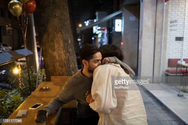 Iranian youth hug each other out of a cafe on Valentines day in downtown Tehran amid the COVID-19 outbreak in Iran on February 14, 2021. Iranian...