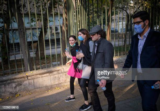 Iranian youth that some of them wearing protective face masks to prevent themselves of infection by the new coronavirus disease walk along an avenue...