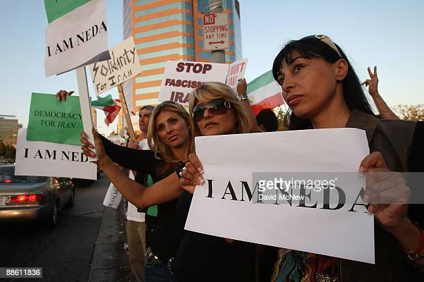Iranian-American women hold signs to identify with a girl known as Neda, believed to be a teenager, who was shot dead at a protest in Tehran, as...