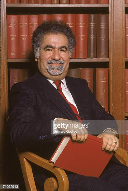 Iranianborn American academic Vartan Gregorian sits in a chair and smiles as he holds a book in his lap at the New York Public Library New York late...