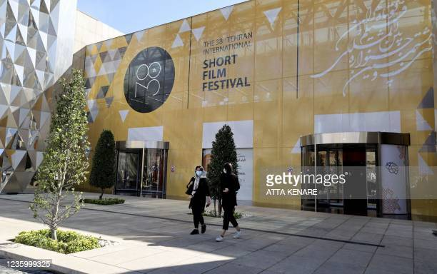 Iranians arrive for the opening day of the 38th Tehran International Short Film Festival in the Iranian capital on October 19, 2021 . - Tehran's...