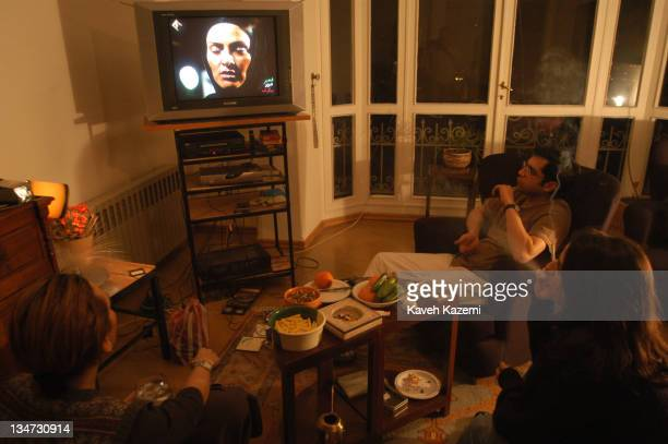 Iranians at home in Tehran watch a veiled woman appearing on national television Iran 2nd February 2003