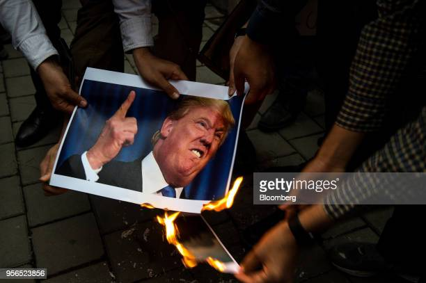 Iranians burn a photograph of US President Donald Trump during an antiUS demonstration outside the former US embassy headquarters in Tehran Iran on...