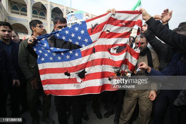 Iranians burn a US flag during a demonstration against American crimes in Tehran on January 3 2020 following the killing of Iranian Revolutionary...