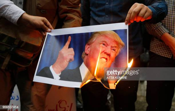 Iranians burn an image of US President Donald Trump during an antiUS demonstration outside the former US embassy headquarters in the capital Tehran...