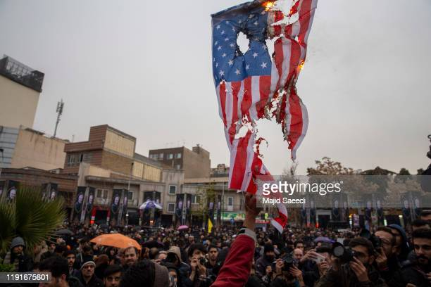 Iranians burn US and Israeli flags during an anti-US protest over the killings during a US air strike of Iranian military commander Qasem Soleimani...