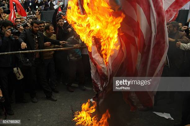 Iranians burn US and Israeli flags outside the former US Embassy in Tehran on November 4 during a demonstration to mark the anniversary of its...