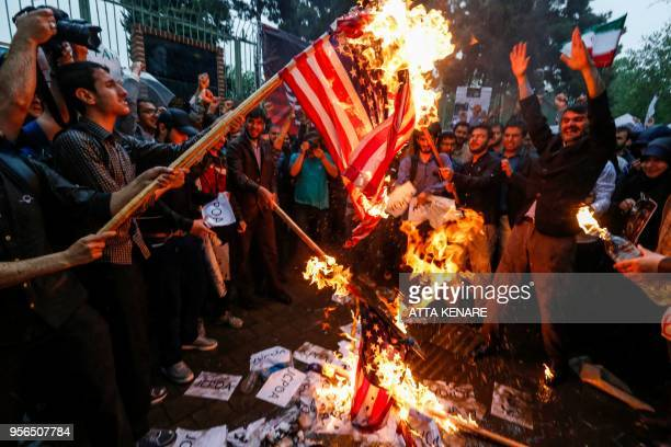 Iranians burn US flags during an antiUS demonstration outside the former US embassy headquarters in the capital Tehran on May 9 2018 Iranians reacted...