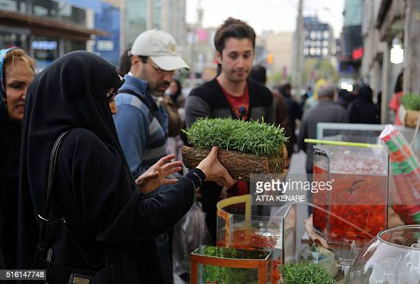 Iranians buy items to celebrate the upcoming Persian new year Noruz at Sadeqyeh Square in Tehran on March 17 2016 Iranians buy flowers green sprouts...