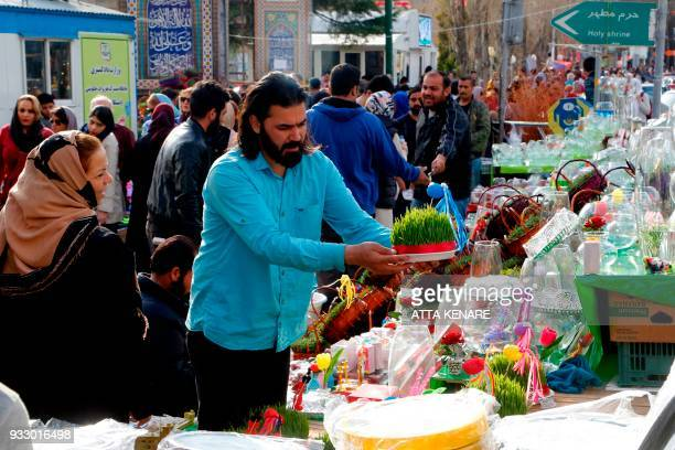 Iranians buy items to celebrate the upcoming Persian new year Noruz at Tajrish in Tehran on March 17 2018 / AFP PHOTO / ATTA KENARE