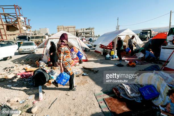 Iranians camp in tents and makeshift shelters outside near damaged buildings in the town of Sarpole Zahab in the western Kermanshah province near the...