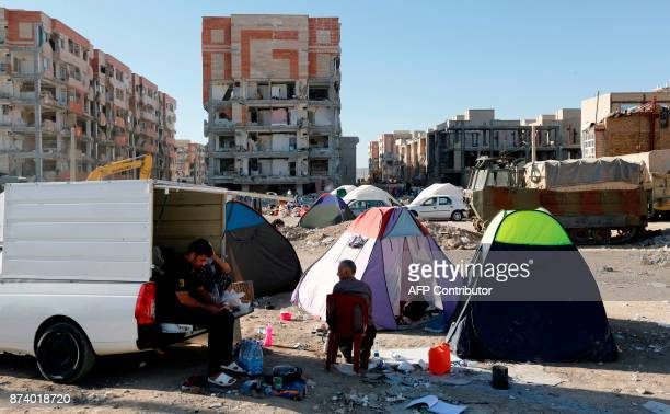 TOPSHOT Iranians camp in tents outside near damaged buildings in the town of Sarpole Zahab in the western Kermanshah province near the border with...