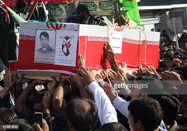 Iranians carry the coffin of an officer in Iran's elite Revolutionary Guards killed the day before during a mass funeral in Zahedan near the...