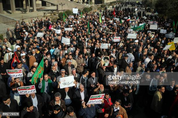 Iranians chant slogans as they march in support of the government near the Imam Khomeini grand mosque in the capital Tehran on December 30 2017 Tens...