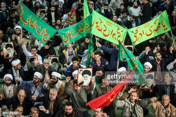 TOPSHOT Iranians chant slogans as they march in support of the government near the Imam Khomeini grand mosque in the capital Tehran on December 30...