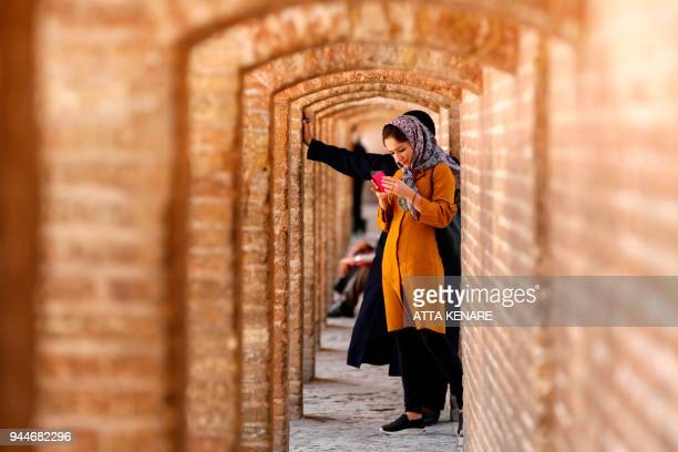 Iranians cross the SioSe Pol bridge over the Zayandeh Rud river in Isfahan on April 6 2018 The 295 metre long bridge was completed in 1596 by Iranian...