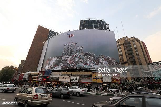 Iranians drive past an antiUS banner inspired by American photographer Joe Rosenthal's iconic World War II photograph Raising the Flag on Iwo Jima on...