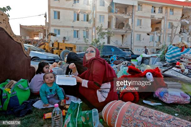 Iranians eat by salvaged belongings outside near damaged buildings in the town of Sarpole Zahab in the western Kermanshah province near the border...