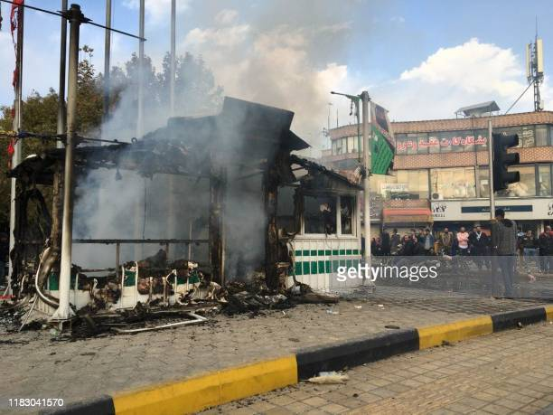 Iranians gather around a charred police station that was set ablaze by protesters during a demonstration against a rise in gasoline prices in the...