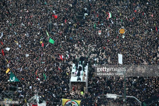 Iranians gather around a vehicle carrying the coffins of slain major general Qassem Soleimani and others as they pay homage in the northeastern city...