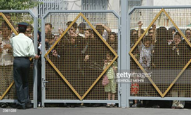 Iranians gather at one of the gates of Tehran's Mehrabad airport to watch the two coffins of Iranian twins Laleh and Ladan Bijani upon their arrival...