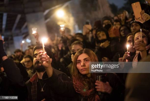 Iranians gather in front of a University and light candles in memory of the victims of the Ukraine Boeing 737 passenger plane in Tehrans business...