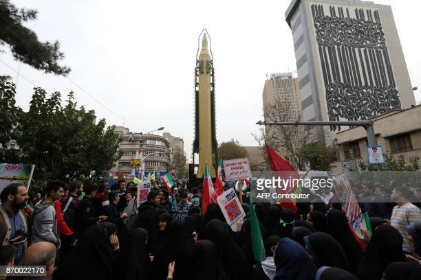 Iranians gather next to a replica of a Ghadr mediumrange ballistic missile during a demonstration outside the former US embassy in the Iranian...